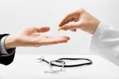 Doktor, der kleine Pille anbietet Stockfotos