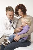 Doktor, der kleines Mädchen überprüft Stockfotos