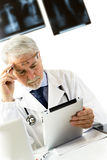 Doktor in der Klinik, die am Schreibtisch betrachtet Röntgenstrahlen auf Tablette sitzt Lizenzfreie Stockfotos