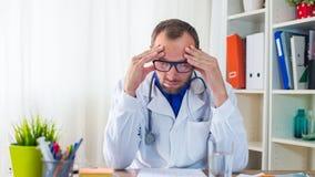 Doktor, der Kopfschmerzen hat. Lizenzfreies Stockbild