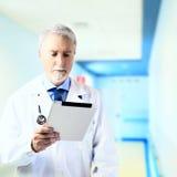 Doktor in der Krankenhaushalle mit Tablette Stockbild