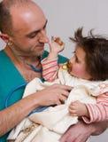 Doktor, der krankes Kind überprüft lizenzfreie stockfotos