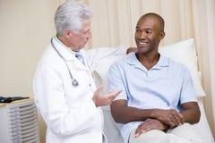 Doktor, der lächelnde Mannüberprüfung gibt Lizenzfreie Stockbilder