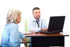 Doktor, der Laptop verwendet und geduldigen Besuch hat stockfotografie
