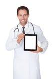 Doktor, der leere digitale Tablette darstellt Lizenzfreies Stockfoto