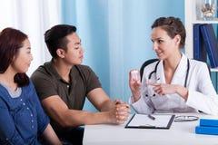 Doktor, der Medizin zu den verschiedenen Paaren gibt Lizenzfreie Stockfotos