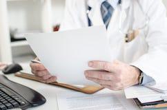 Doktor, der medizinische Anmerkungen liest Stockfotografie