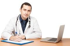Doktor, der medizinisches Dokument ergänzt Stockfotos