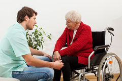Doktor, der mit behindertem Patienten spricht Lizenzfreie Stockbilder