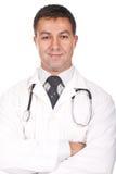 Doktor, der mit den Armen gekreuzt und dem Lächeln steht Lizenzfreie Stockbilder