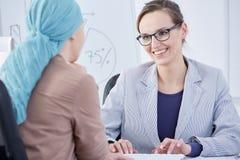 Doktor, der mit einem Patienten schreibt und spricht Stockfoto