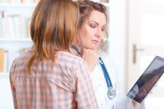 Doktor, der mit einem Patienten spricht Lizenzfreie Stockfotografie