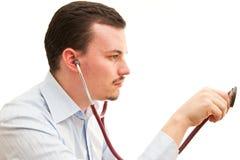 Doktor, der mit einem Stethoskop hört lizenzfreies stockbild