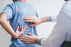 Doktor, der mit geduldiger Rückenproblem-Physiotherapie Co sich berät stockbild