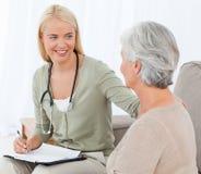 Doktor, der mit ihrem Patienten spricht Lizenzfreies Stockbild