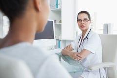 Doktor, der mit ihrem Patienten spricht Stockbilder