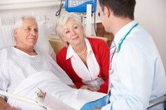 Doktor, der mit Paaren auf BRITISCHEM Krankenhaus spricht Lizenzfreie Stockbilder