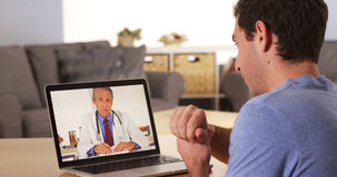 Doktor, der mit Patienten über Webcam spricht Stockbild