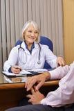 Doktor, der mit Patienten in ihrem Büro spricht Stockfotos