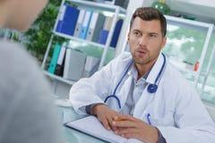Doktor, der mit Patienten während des Besuchs spricht Stockbilder