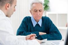 Doktor, der mit seinem Patienten spricht Stockfotografie