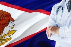 Doktor, der mit Stethoskop auf Amerikanisch-Samoa-Flaggenhintergrund steht Nationales Gesundheitssystemkonzept, medizinisches The lizenzfreies stockfoto