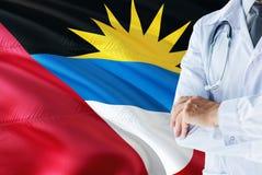 Doktor, der mit Stethoskop auf Antigua und Barbuda-Flaggenhintergrund steht Nationales Gesundheitssystemkonzept, medizinisches Th stockfotos