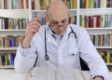 Doktor, der oben Informationen über Medizin schaut Lizenzfreies Stockfoto