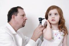 Doktor, der Ohr des kleinen Mädchens überprüft stockfotografie