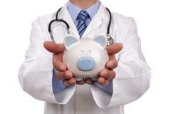 Doktor, der piggy Querneigung anhält Stockbild