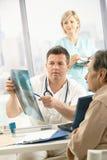 Doktor, der Röntgenstrahlbild mit Patienten behandelt Lizenzfreie Stockfotos