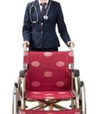 Doktor, der Rollstuhl drückt Stockbild