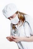 Doktor in der schützenden Schablone mit Thermometer Stockfotos