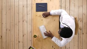 Doktor, der an Schreibtisch mit Laptop-Computer arbeitet stock footage