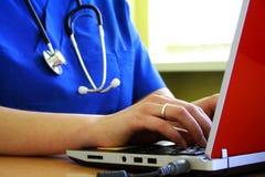 Doktor, der am Schreibtisch mit Laptop-Computer sitzt stockfotografie