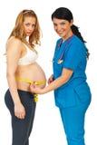 Doktor, der schwangeren Bauch misst Stockfoto