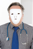 Doktor, der sein Gesicht mit weißer Maske bedeckt Stockbild
