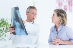 Doktor, der seinem Patienten Röntgenstrahl zeigt Stockfoto