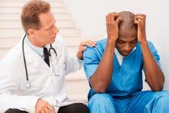 Doktor, der seinen Kollegen tröstet Lizenzfreies Stockfoto