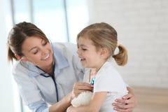 Doktor, der Stethoskop auf kleinem Mädchen verwendet Lizenzfreie Stockfotos