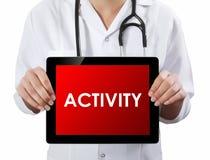 Doktor, der Tablette mit TÄTIGKEITS-Text zeigt Lizenzfreies Stockbild