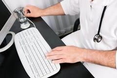 Doktor an der Tastatur Stockbild