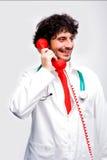 Doktor, der am Telefon lächelt und spricht Stockfotografie
