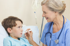 Doktor, der Temperatur des Jungen-Kind-Patienten nimmt Stockbild