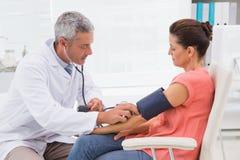 Doktor, der Test an seinem Patienten durchführt Stockbild
