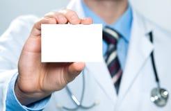 Doktor, der unbelegte Visitenkarte anhält lizenzfreie stockfotos