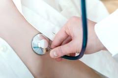 Doktor, der unter Verwendung des Stethoskops überprüft Lizenzfreie Stockbilder