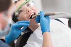 Doktor, der Zähne von abgehendem Mädchen kuriert Lizenzfreie Stockfotografie