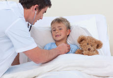 Doktor, der zu einem Kind breaht hört Stockbilder