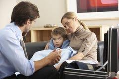 Doktor, der zu Hause krankes Kind und Mutter besucht stockfotografie